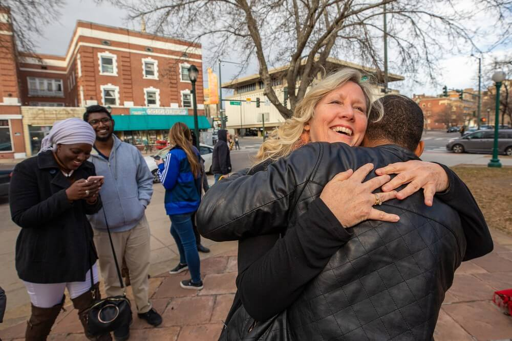 american woman smiles and hugs african international student