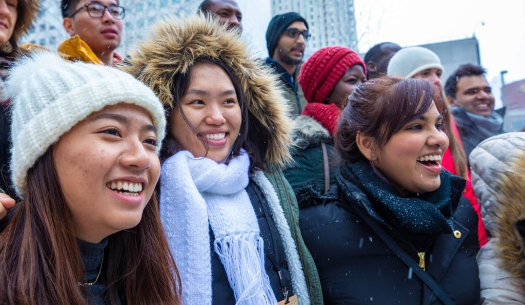 Group of international students smiling in the light snow
